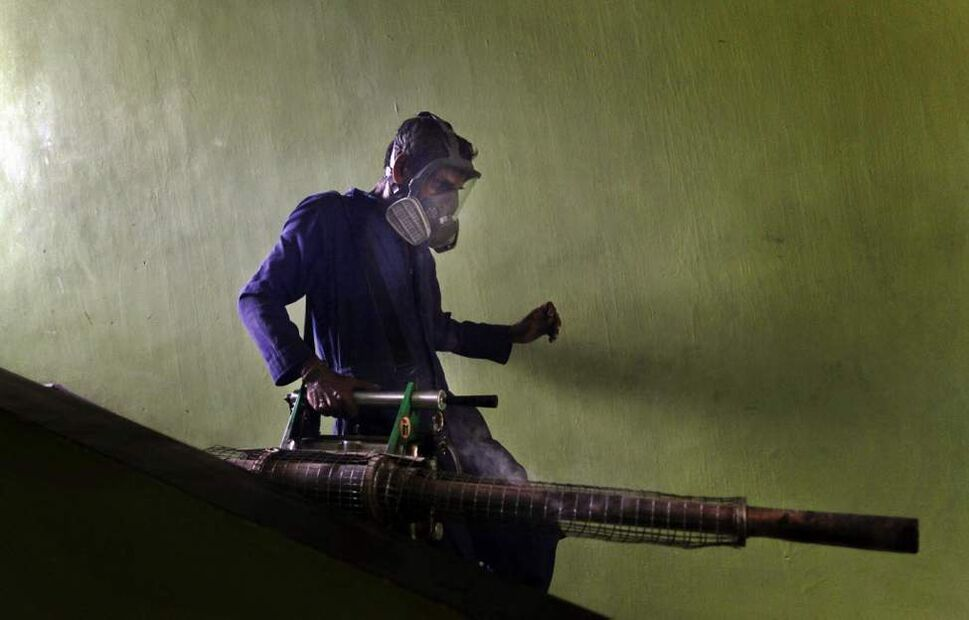 A Sri Lankan municipal worker walks down stairs after fumigating for a public housing scheme in an attempt to control dengue fever in Colombo, Sri Lanka. More than 10,000 security forces have been deployed in Sri Lanka to help eliminate mosquito-breeding grounds in a bid to contain the dengue fever that has killed more than 74 people and infected 15,000 others so far this year. (AP Photo/Gemunu Amarasinghe)