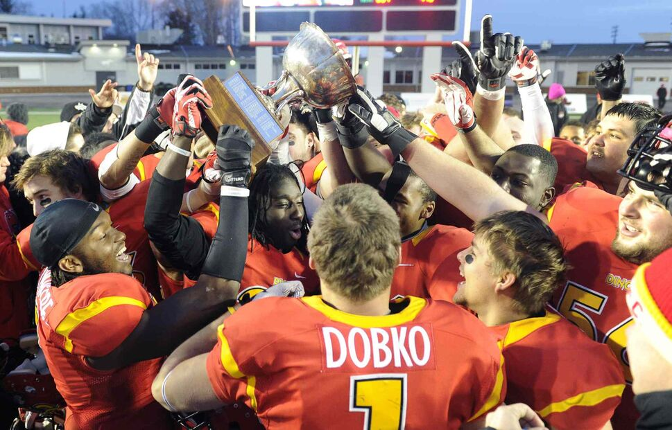 Dinos players raise the Hardy Cup after defeating the University of Manitoba Bisons. (Larry MacDougal / The Canadian Press)