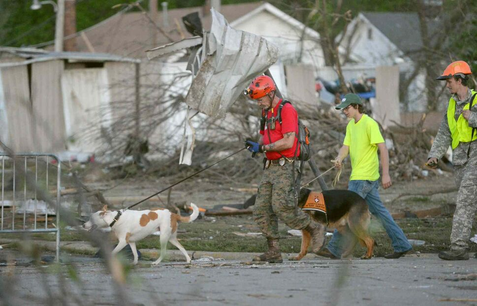 A K-9 rescue unit walks along Military Street in Baxter Springs, Kan., as they survey the damage from Sunday's tornado. (ROGER NOMER / THE JOPLIN GLOBE / THE ASSOCIATED PRESS)