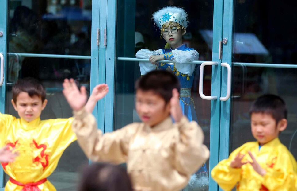 A young performer from the Great Wall Performing Arts school watches another group rehearse during Asian Heritage Month celebrations at The Forks, Sunday. (TREVOR HAGAN / WINNIPEG FREE PRESS)