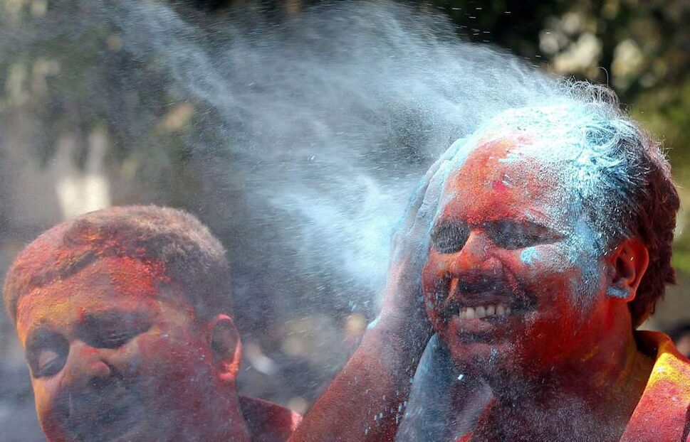 A man reacts as his face is smeared with colored powder during Holi festivities in Mumbai, India, Thursday, March 8, 2012. Holi, the Hindu festival of colors, also heralds the coming of spring. (AP Photo/ Rajanish Kakade) (CP)