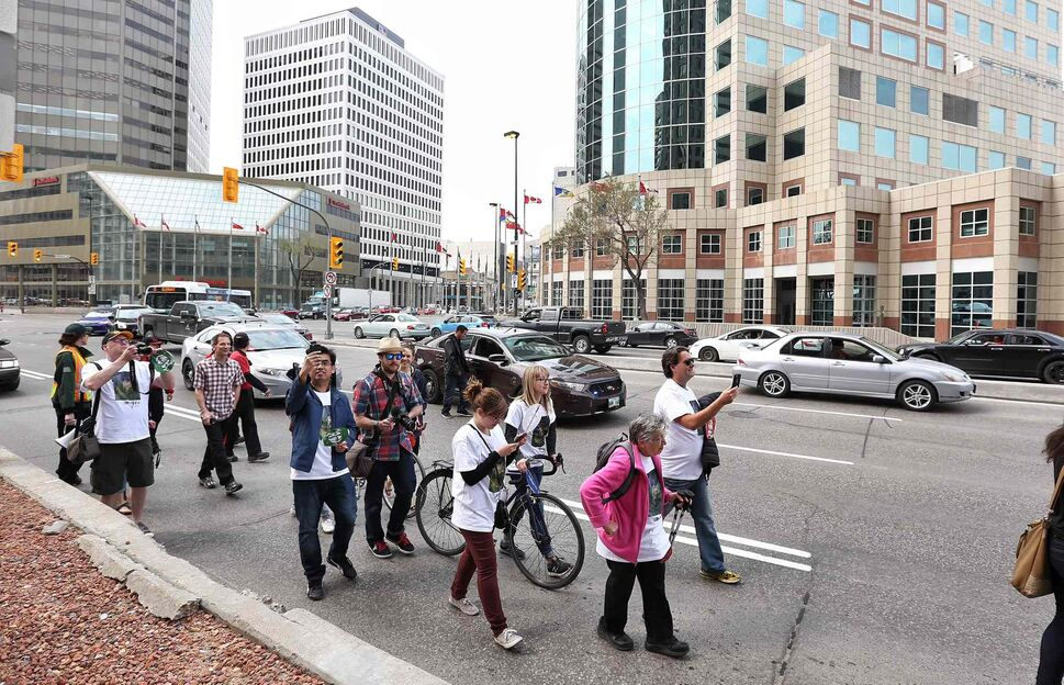Participants in the City Crossing Jane's Walk make their way through the intersection of Portage Avenue and Main Street. (MIKE DEAL / WINNIPEG FREE PRESS)