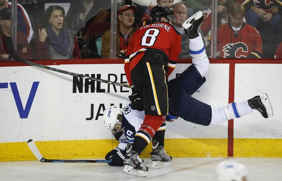 Winnipeg Jets' Tobias Enstrom, left, gets upended by Calgary Flames' Joe Colborne during third period in Calgary Thursday. (Jeff McIntosh / The Canadian Press)