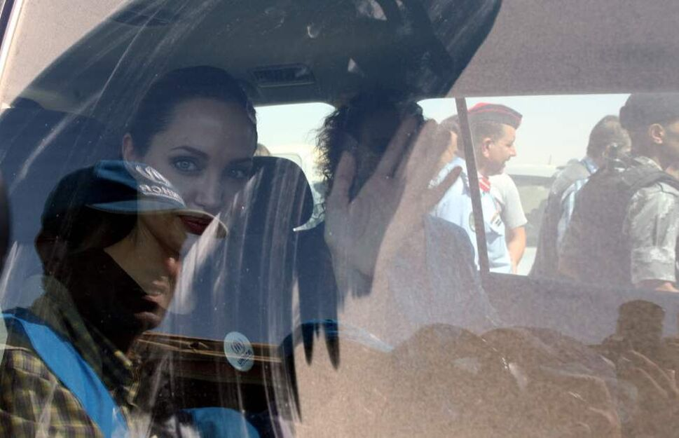 "The U.N. refugee agency's special envoy, actress Angelina Jolie, waves through the dusty window of her car as she departs the Zaatari Refugees Camp in Jordan for Syrians who fled the civil war in their country. Jolie said she heard ""horrific"" and ""heartbreaking"" accounts from Syrian refugees in a camp which hosts about 30,000 Syrians displaced by the 18-month conflict that has so far claimed at least 23,000 lives, according to activists. (AP photo/Mohammad Hannon)"