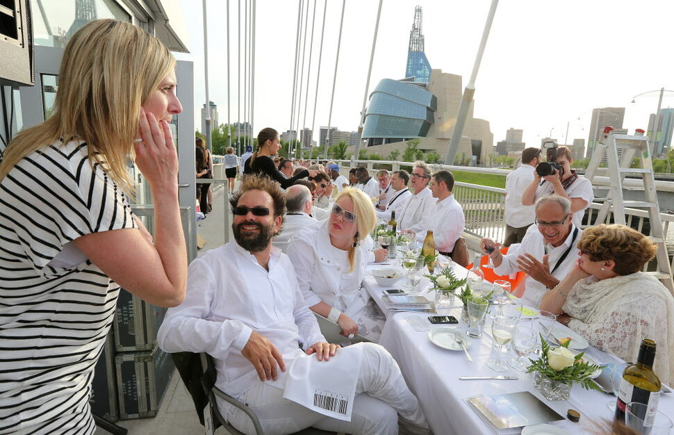 Table for 1200 event organizers Anna Hurme (third left) and Sasa Radulovic (second left) chat with diners at the VIP table on the Esplanade Riel Bridge.  (Jason Halstead / Winnipeg Free Press)