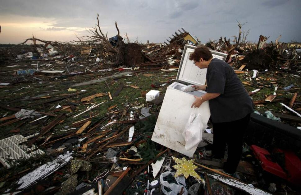 Anita Stokes salvages meat from a freezer at her home that was destroyed by a tornado in Joplin, Mo., Monday, May 23, 2011. A large tornado moved through much of the city Sunday, damaging a hospital and hundreds of homes and businesses and killing at least 116 people. (AP Photo/Charlie Riedel) (CP)