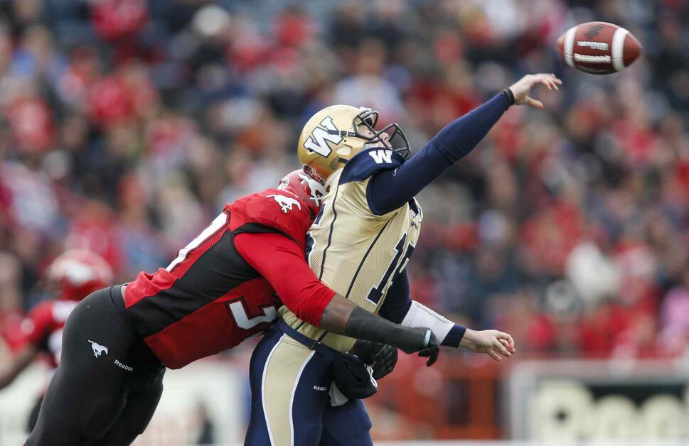 Winnipeg Blue Bombers quarterback Max Hall takes a hard hit from Calgary Stampeders' Charleston Hughes during the first half. (Jeff McIntosh / The Canadian Press)