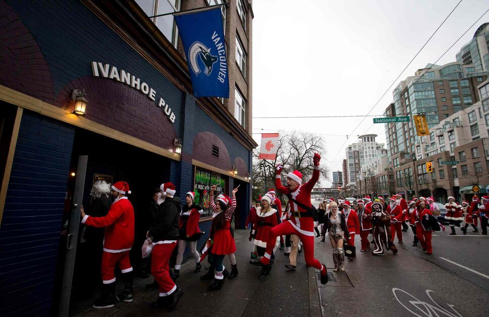 Hundreds of people dressed as Santa Claus converge on a pub during a Santacon event in Vancouver, B.C. on Saturday. (DARRYL DYCK / THE CANADIAN PRESS)