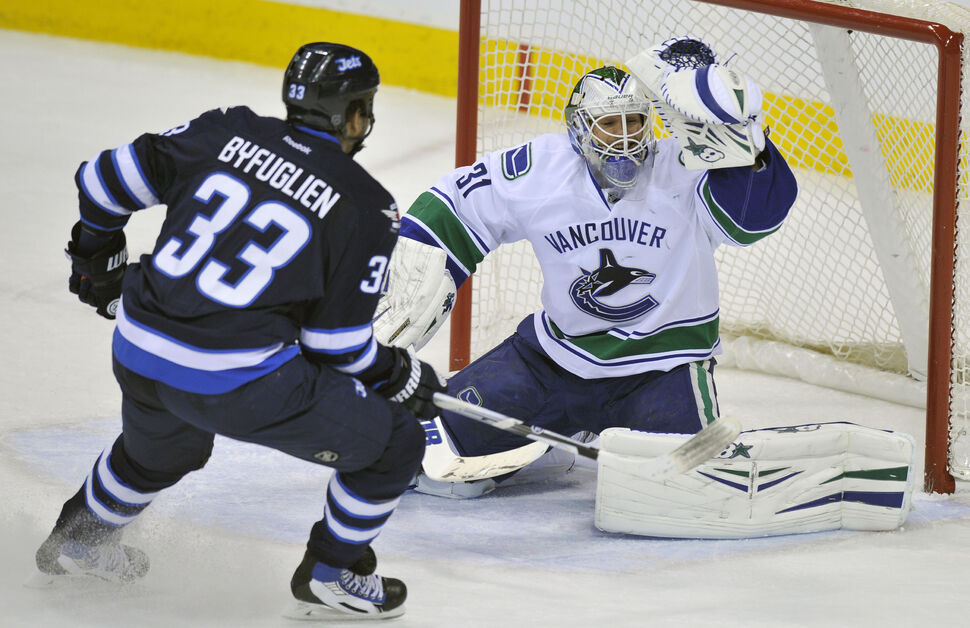 Winnipeg Jets' Dustin Byfuglien runs at  Vancouver Canucks' goaltender Eddie Lack  during the first period of Friday's game at Winnipeg's MTS Centre. ( Fred Greenslade  / Special for the WINNIPEG FREE PRESS)
