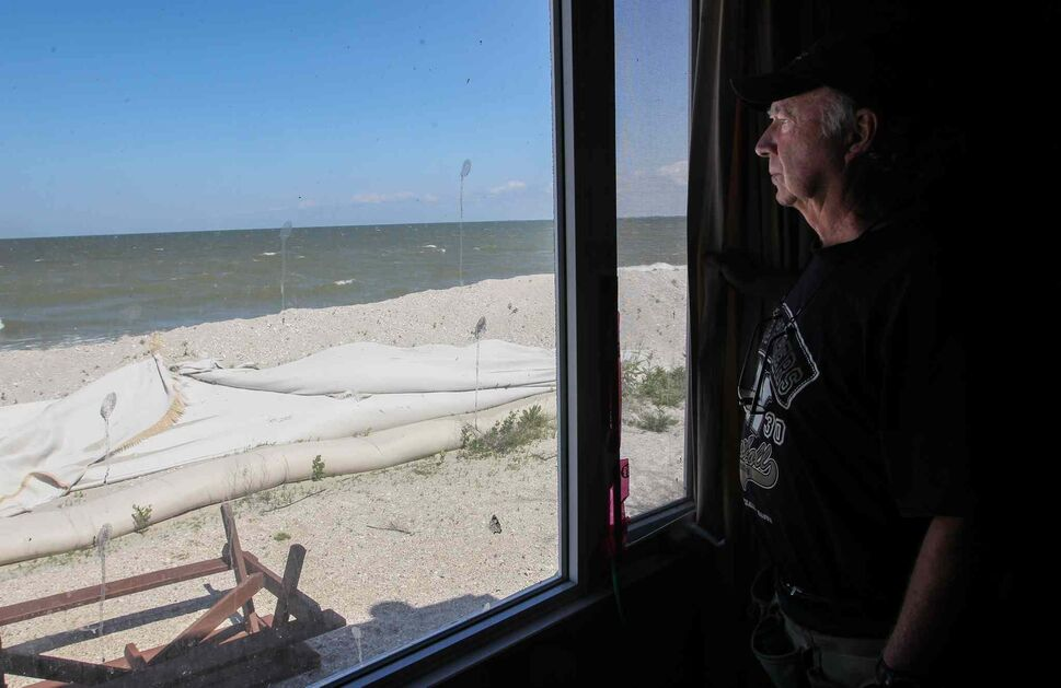 Frank Renouf looks out the window of his niece's cottage. The cottage is protected by a tube dike that runs along the beach at Twin Lakes Beach. Some of the tubes have been damaged by ice from last winter and his family is concerned they won't hold in the coming weeks. (Mike Deal / Winnipeg Free Press)