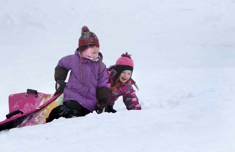 Five-year-old Emily Aikman, right, giggles as she pushes her sled up Omand's Creek hill with her friend Mya Tottle, 5, Saturday morning while they enjoyed the warm winter weather with their families. (Ruth Bonneville / Winnipeg Free Press)