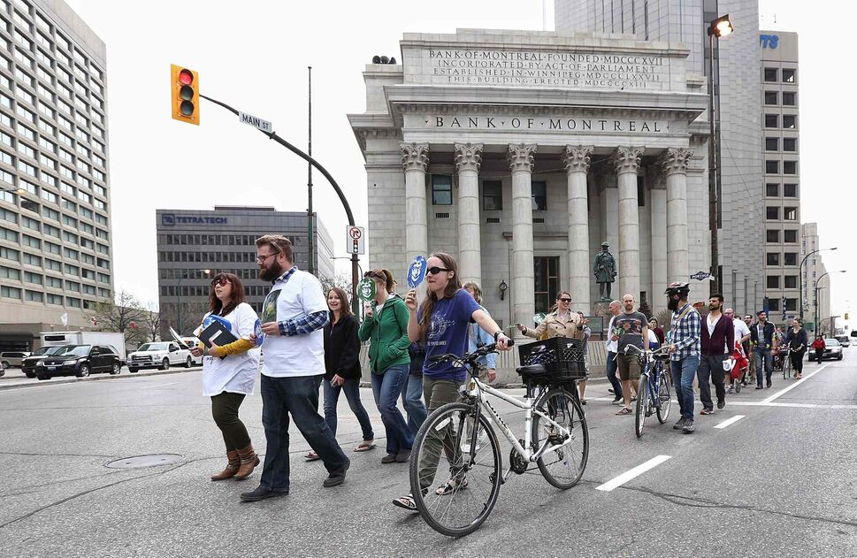 Participants in the City Crossing Jane's Walk make their way through the intersection of Portage Avenue and Main Street, which has been closed off to pedestrian traffic since the late 1970s. Some of the pedestrians carried masks depicting Jane Jacobs' face to symbolize looking at the city through Jane's perspective. (MIKE DEAL / WINNIPEG FREE PRESS)