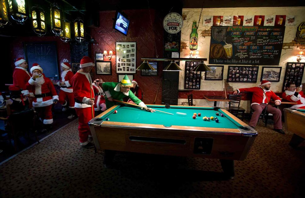 A man dressed as the character Buddy from the movie 'Elf' and a man dressed as Santa Claus play pool at a pub. (DARRYL DYCK / THE CANADIAN PRESS)