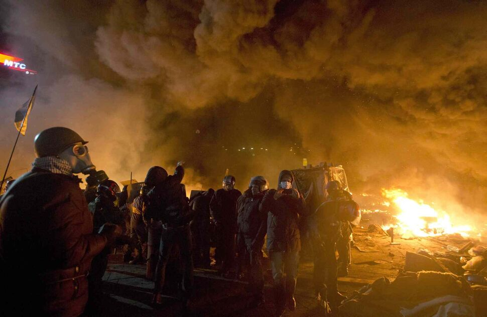 Anti-government protesters clash with riot police in Kiev's Independence Square, the epicentre of the country's current unrest. Thousands of police armed with stun grenades and water cannons attacked the large opposition camp in Ukraine's capital on Tuesday that has been the centre of nearly three months of anti-government protests after several people were killed in street clashes.  (Efrem Lukatsky / The Associated Press)