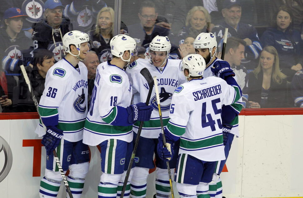 Canucks celebrate goal by Alexandre Burrows in the second period.    (BORIS MINKEVICH / WINNIPEG FREE PRESS)