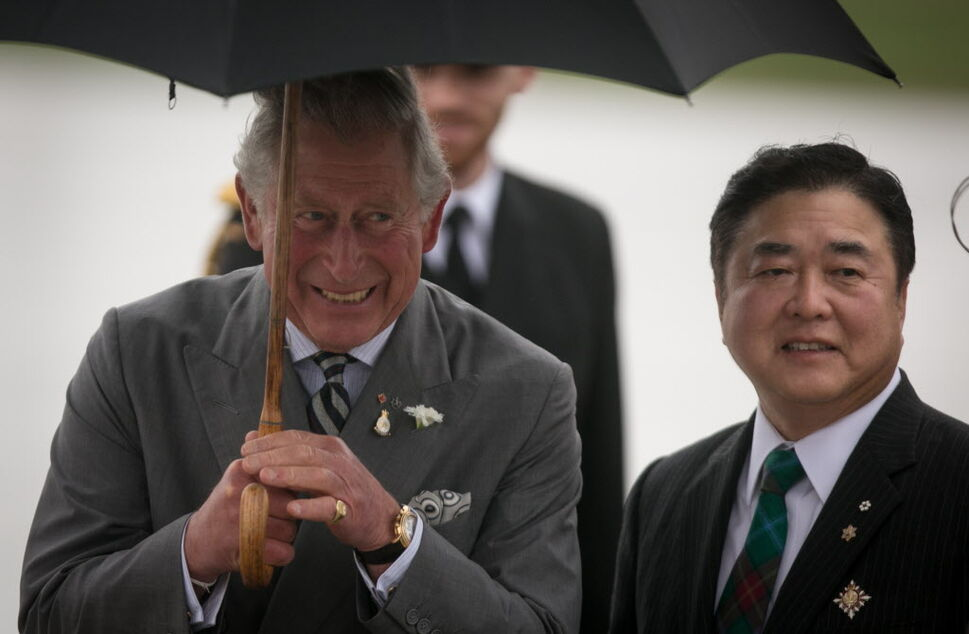 Prince Charles laughs with Lt. Gov. Philip Lee after a wet and windy arrival.  (Melissa Tait / Winnipeg Free Press)