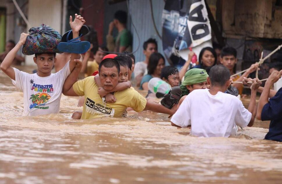 Residents hang on to a rope as they pass strong currents along a flooded area in Marikina, Philippines. A fresh deluge forced more evacuations along fast-rising rivers in the Philippine capital Thursday, as the city and surrounding areas struggled to deal with widespread flooding triggered by nearly two weeks of relentless rains. (AP Photo/Aaron Favila)