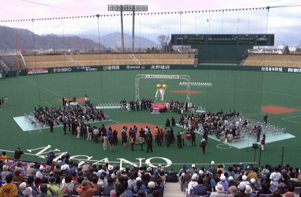 In this April 16, 2000 photo, a ceremony is held to unveil a baseball stadium, also known as the Olympic Stadium, which was used for the opening and closing ceremony for the 1998 Nagano Winter Olympics, in Nagano, central Japan. (Kyodo News / The Associated Press)