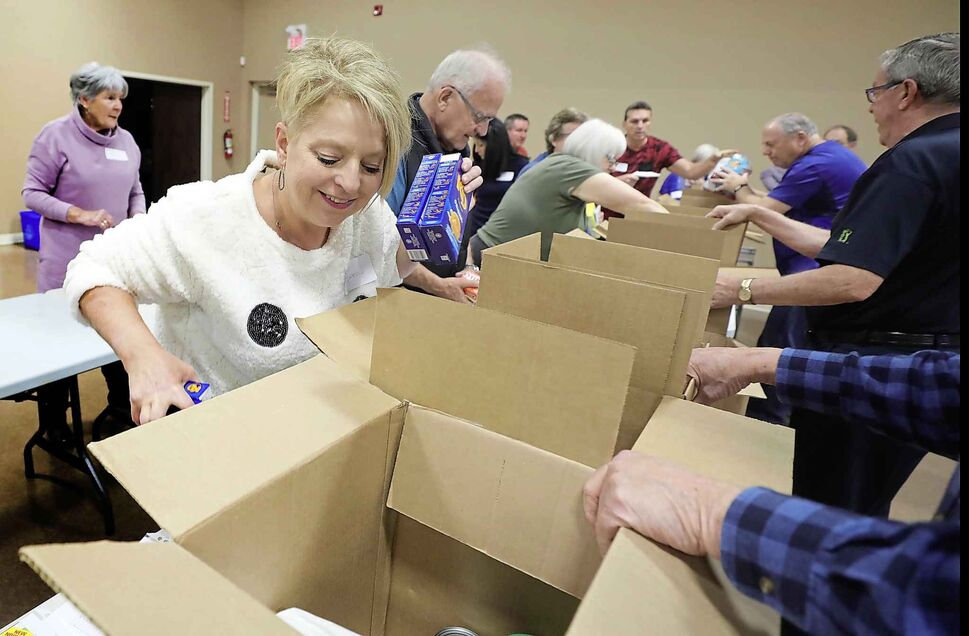 Charleswood United church members volunteer their time to pack 50 hampers for the Christmas Cheer Board. (Ruth Bonneville / Winnipeg Free Press)