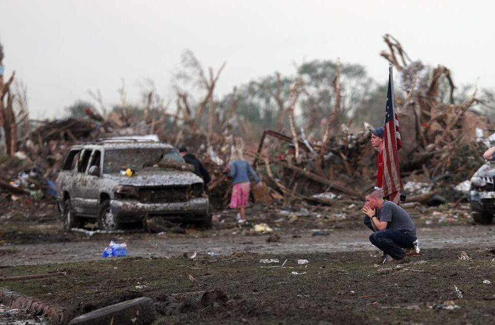 People react in front of the Plaza Towers Elementary school in Moore following a deadly tornado. (Sarah Phipps / The Oklahoman)