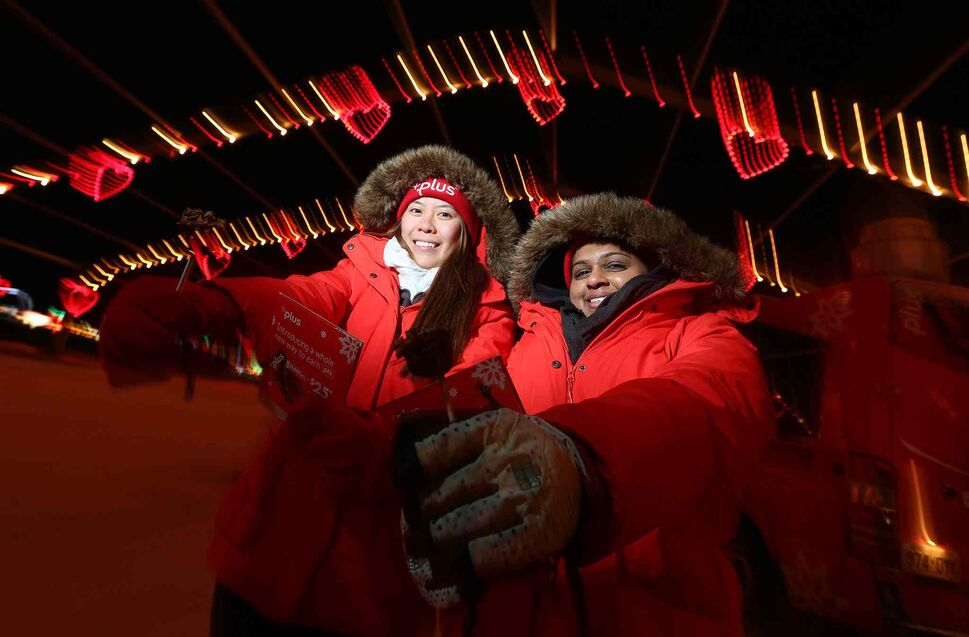 Michelle Truong (left) and Alissa Patel hand out sweet treats as part of a promotion at Canad Inns Winter Wonderland. (Jason Halstead / Winnipeg Free Press)