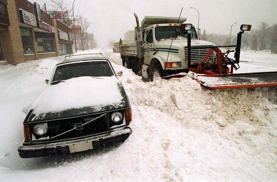 A City of Winnipeg snowplow works around vehicles on Portage Avenue on Sunday, April 6. The city had come to a virtual standstill. (Jeff DeBooy / Winnipeg Free Press files)