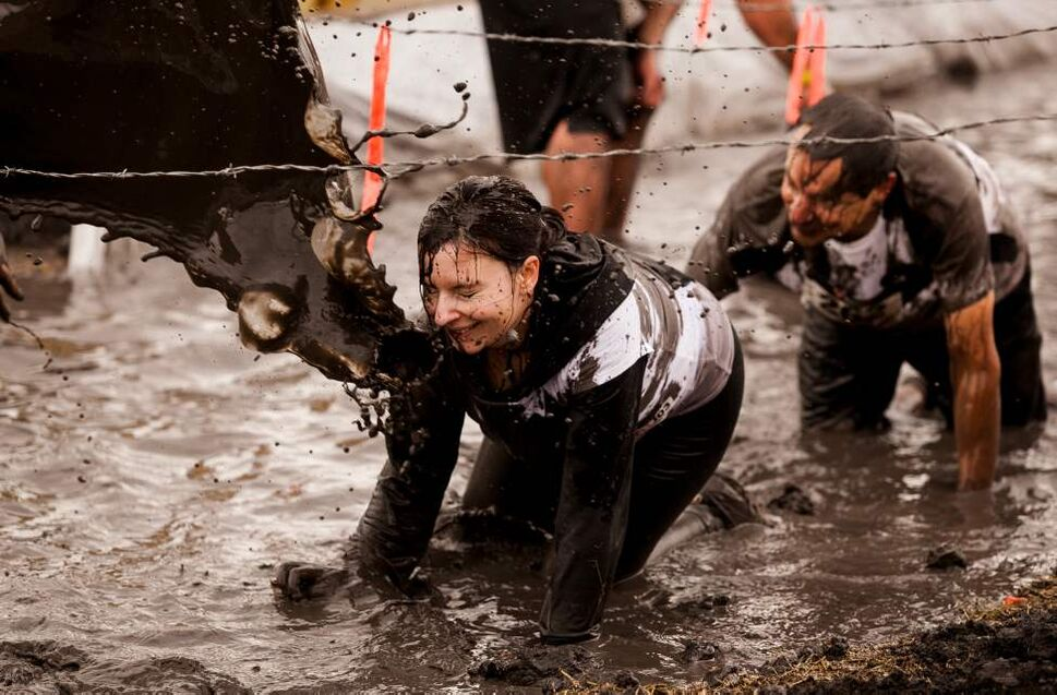 Laura Gallant braces for a splash of muddy water near the finish line of the Dirty Donkey Mud Run on Saturday morning. (Melissa Tait / Winnipeg Free Press)