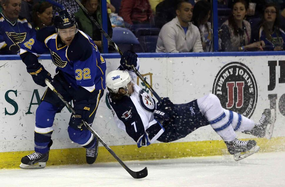 Jets defenceman Keaton Ellerby falls to the ice after being checked into the boards the Blues' Chris Porter during the second period. (JEFF ROBERSON / THE ASSOCIATED PRESS)