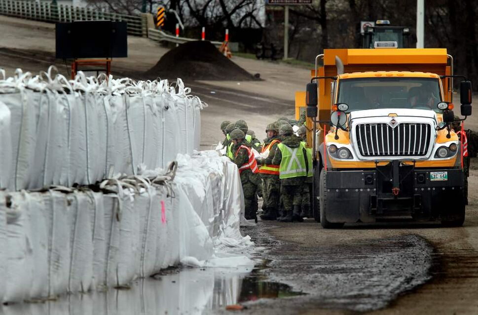 Soldiers hand balm sandbags to reinforce superbags along First Street in Brandon adjacent to Dinsdale Park. May 12, 2011. (Phil Hossack / Winnipeg Free Press)