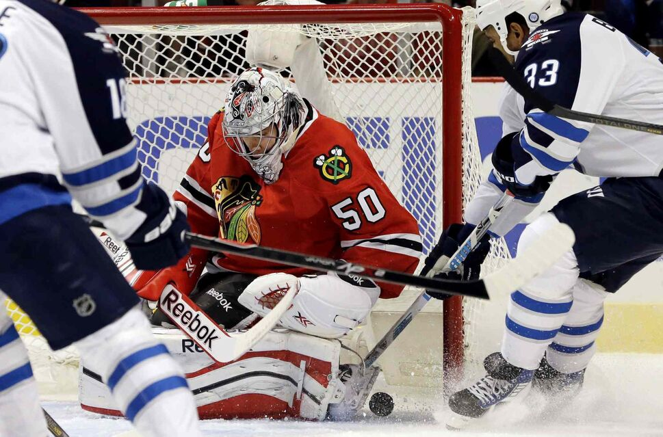 Chicago Blackhawks goalie Corey Crawford (50) saves a shot by Winnipeg Jets defenceman Dustin Byfuglien (33) during the first period. (Nam Y. Huh / The Associated Press)