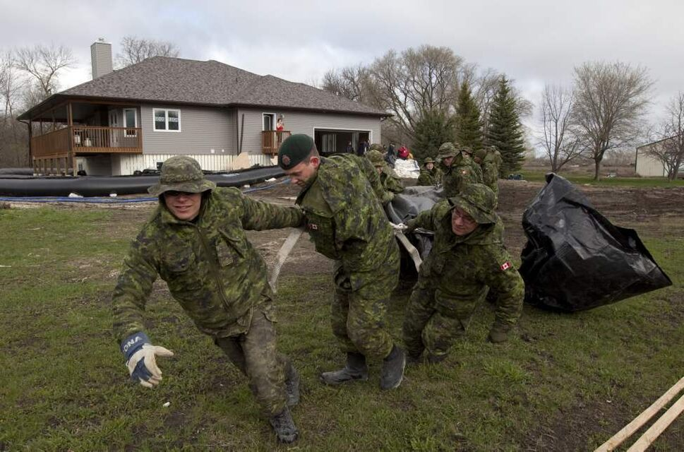 Members of the Canadian Forces surround a home with a water dike close to the Hoop and Holler Bend near Portage La Prairie, Man, Thursday, May 12, 2011.   THE CANADIAN PRESS/Jonathan Hayward