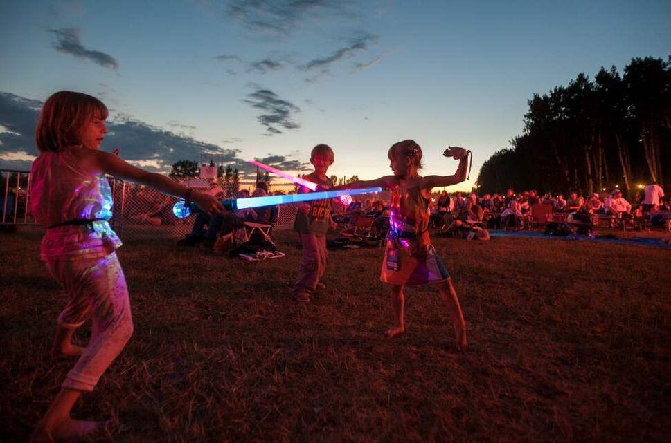 Audenne Derksen (left), 7, plays with her cousin Nicklas Hamm, 6, and sister Arielle, 7, at the 2012 Winnipeg Folk Festival on Saturday.  Melissa Tait / Winnipeg Free Press