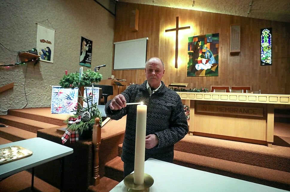 Tom Sturdy lights his candle from the lit Christ candle at  the front of Trinity United Church for their Longest Night of the Year Worship service on Dec. 21. The annual event takes place on solstice and is a quiet, thoughtful service for those who find this time of year difficult.   (Ruth Bonneville / Winnipeg Free Press)