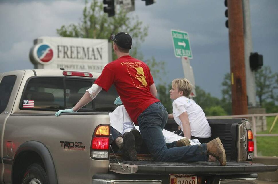 A pickup truck with what looked like two rescue workers and two injured people weaves in and out of traffic to get to Freeman Hospital West in Joplin, Mo. after the town was hit by a tornado on Sunday. (Jaime Green / The Associated Press)