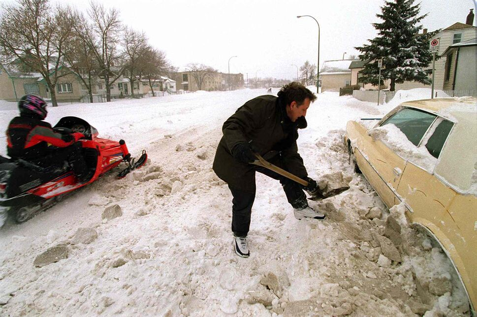 As a snowmobile passes, Winnipegger Rick Tanchuk digs out his car that was buried by a passing snowplow on McPhillips Street near Burrows Avenue.  (Jeff DeBooy / Winnipeg Free Press files)