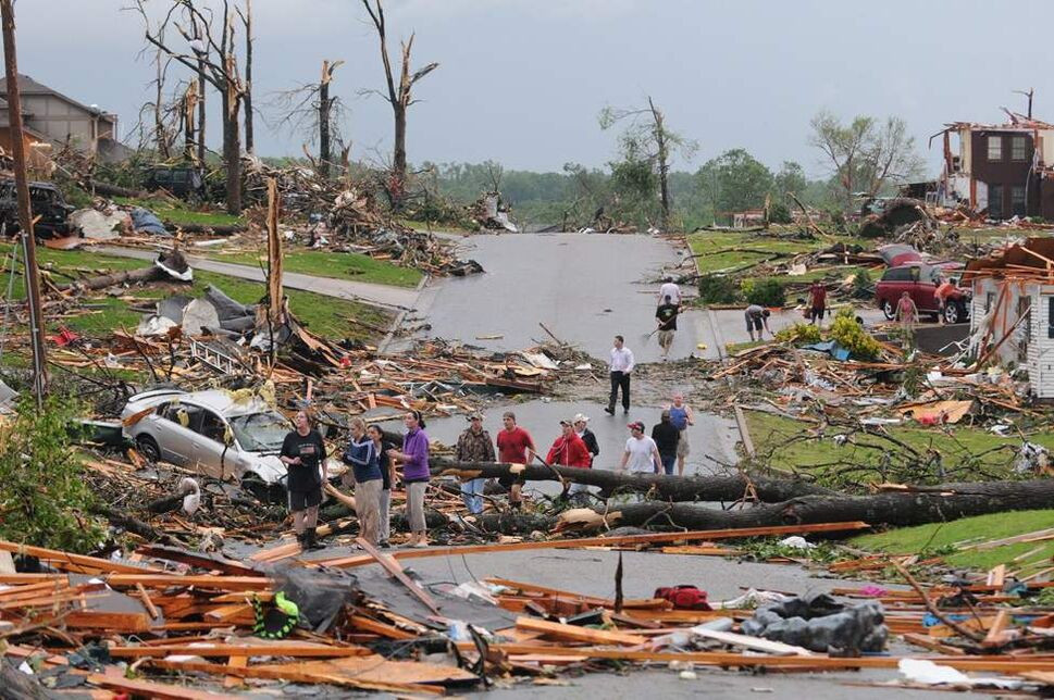 Residents of Joplin, Mo, survey the damage after a tornado hit the city on Sunday, May 22, 2011. The tornado tore a path a mile wide and four miles long destroying homes and businesses. (Mike Gullett / The Associated Press)