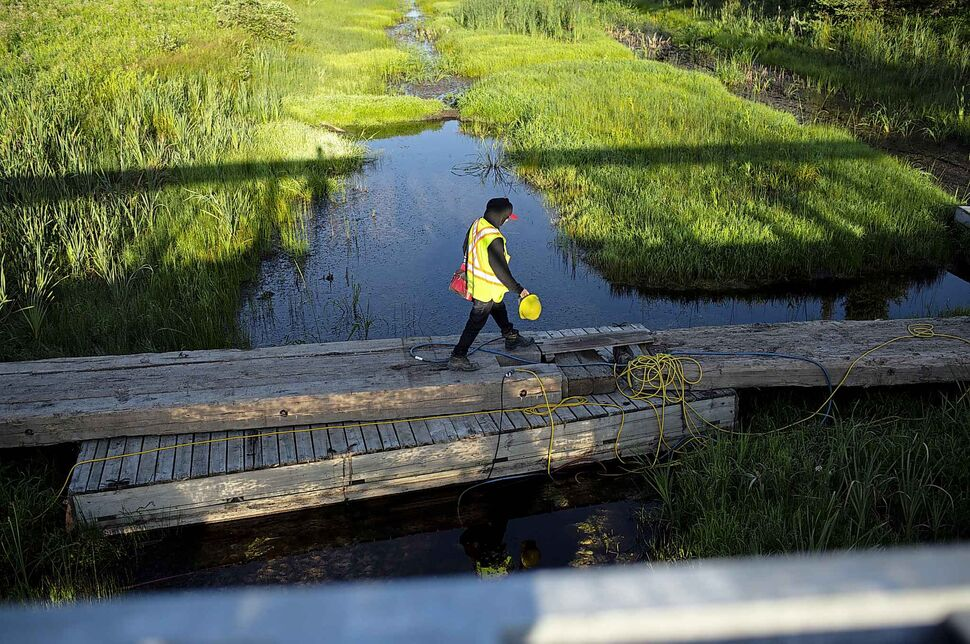 Rock truck driver and Shoal Lake 39 resident Davidson walks across the Winnipeg aquaduct which pumps water from Shoal Lake to the city towards Freedom Road. (ANDREW RYAN / WINNIPEG FREE PRESS)