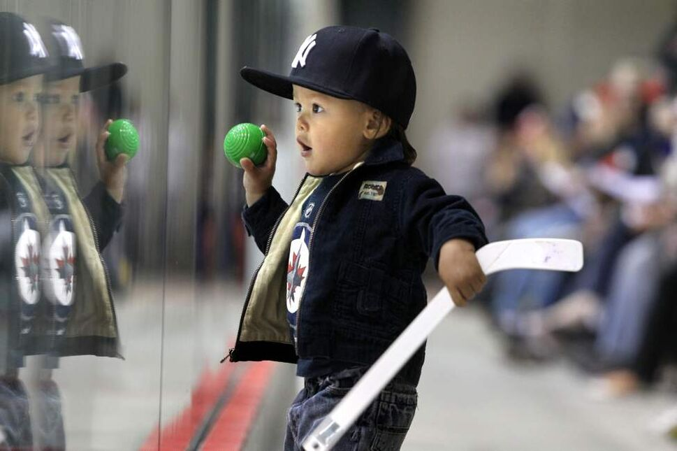 Seventeen-month-old Rocco Nakoyak peers through the glass in wonderment as the Winnipeg Jets make their first on-ice appearance in front of a full house of hockey fans during their public open house  practice Saturday morning.