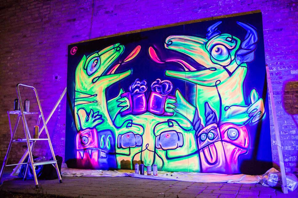 A black light graffiti painting by Pink Panda in front of PEG Beer Co. during Nuit Blanche.
