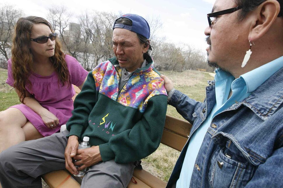 May 5, 2009: Faron Hall reflects on jumping in the Red River to save a 14-year-old boy Sunday as he speaks with the Free Press Tuesday from the bench he sleeps on. Here he is comforted by Morris Shannacappo, Southern Grand Chief and Nahanni Fontaine of the Southern Chiefs Organization. They are getting him shoes, a hotel room and a ride to Dakota Tipi to see his father, whom he hasn't seen for nine years.  (MIKE APORIUS/WINNIPEG FREE PRESS Files)