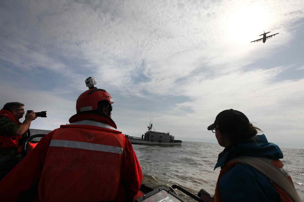 Rescue crews and media watch as a Hercules aircraft flies overhead. (Ruth Bonneville / Winnipeg Free Press)