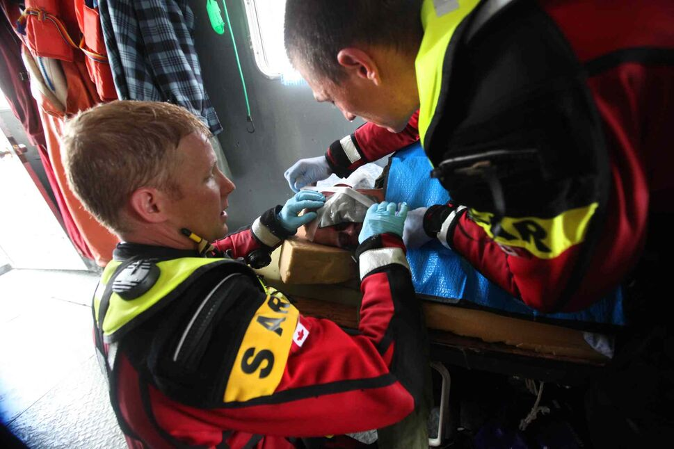 SAR techs work together to aid the victim. (Ruth Bonneville / Winnipeg Free Press)