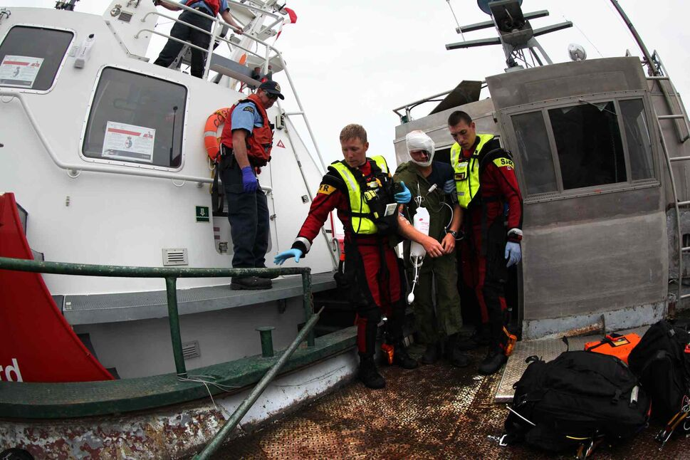 SAR techs help the victim out to the deck of the ship. (Ruth Bonneville / Winnipeg Free Press)
