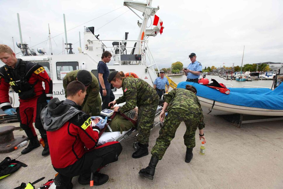 Back on land, rescue personnel tend to the victim. (Ruth Bonneville / Winnipeg Free Press)