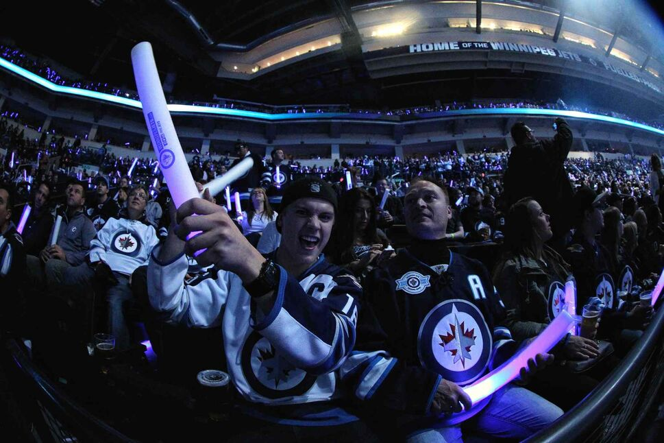 Brayden Carriere and his father Troy cheer as the Winnipeg Jets hit the ice. (MIKE DEAL / WINNIPEG FREE PRESS)