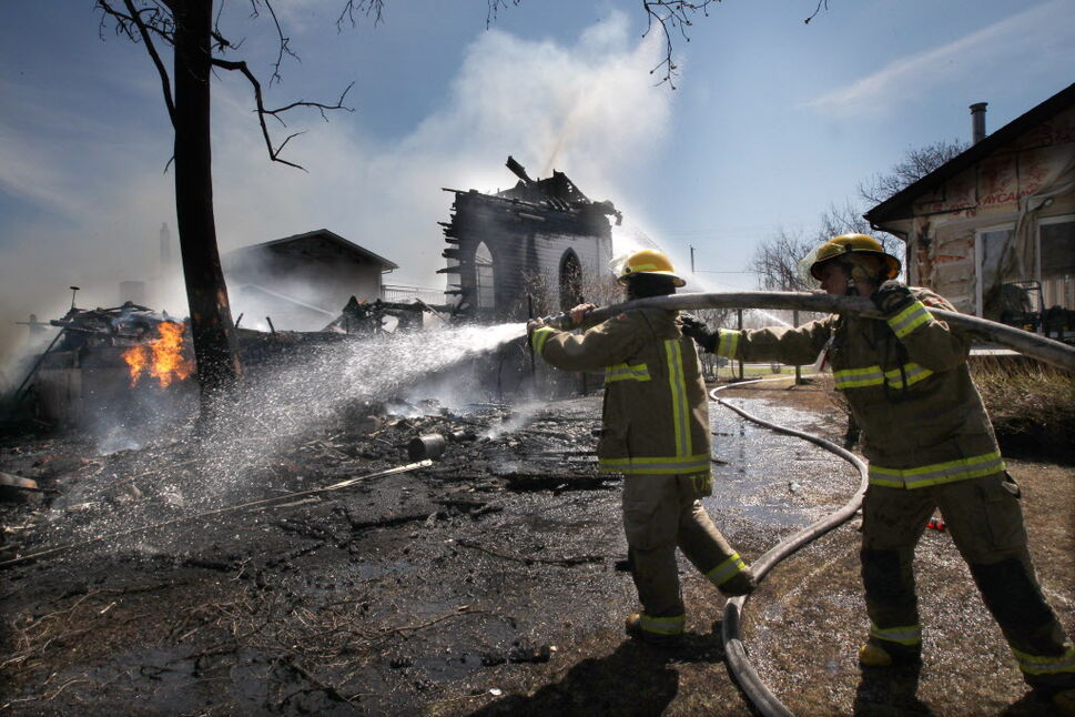 The Starbuck United Church in Starbuck, Manitoba caught fire and is a total loss Friday. Firefighters keep the fire under control near 3 p.m. to prevent it from spreading to homes on either side of the structure. (JOE BRYKSA / WINNIPEG FREE PRESS)