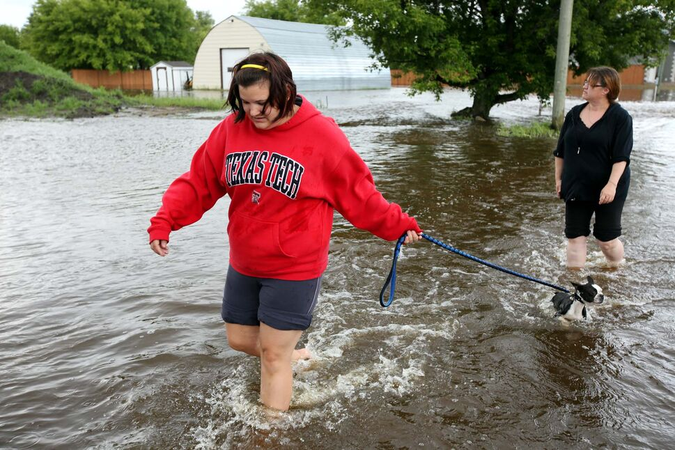 Lindsay Robinson, her dog Diesel and Tamara Miller walk through flood waters on Bridge Street in Virden as the Gopher Creek continues to rise on Monday afternoon.   (Tim Smith / Brandon Sun)