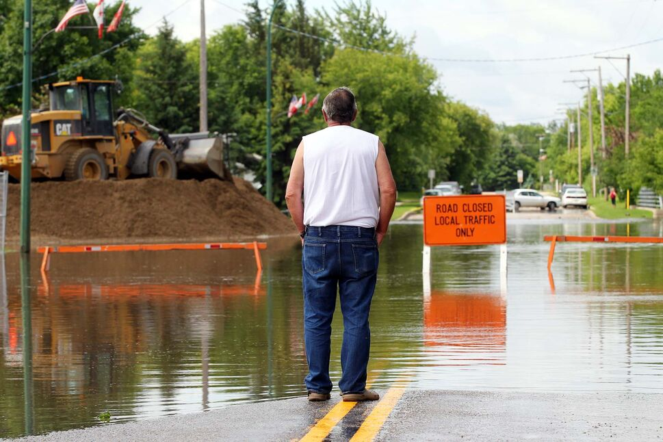 John Higginbotham watches as a dike is built to protect a lift station along King Street in Virden as the Gopher Creek continues to rise on Monday afternoon. (Tim Smith / Brandon Sun)