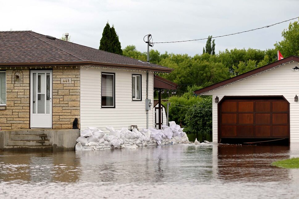 Brandon Sun 30062014 Sandbags surround a portion of a home inundated with water in the town of Virden as the Gopher Creek continued to rise on Monday. Tim Smith/Brandon Sun) (Tim Smith/Brandon Sun)