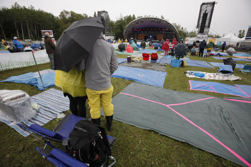 Festivalgoers wait for a performance despite the rainy weather conditions on the final day of the Winnipeg Folk Fest Sunday, July 13, 2014. John Woods / Winnipeg Free Press (John Woods / Winnipeg Free Press)